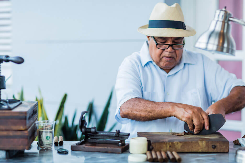A cigar rollers demonstrates his art at an exclusive party.